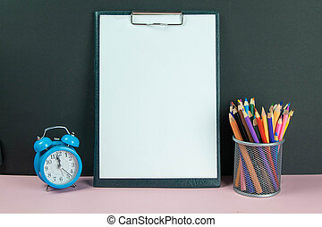 Tablet with white sheet a4 next to a glass with colored pencils and blue alarm clock
