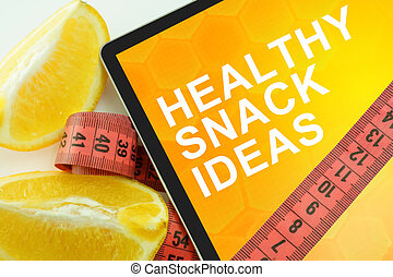Tablet with words healthy snack ideas and measuring tape on white background