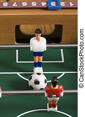 tabletop soccer - playing tabletop soccer with red and...
