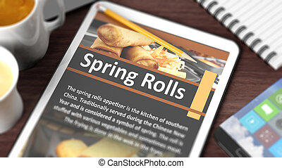 "Tabletop with various objects focused on tablet with recipe of ""Spring Rolls"" on screen"