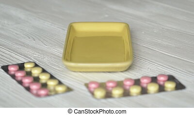 Tablets fall in the container mounted on the table