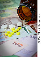 tablets on thai banknotes (baht) for medication concept.