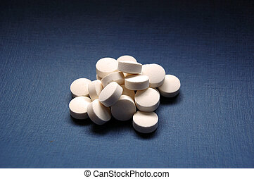 Tablets - Stack of white tablets on blue background