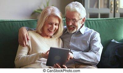 tablette, délassant, sofa, couple, rire, numérique, utilisation, personne agee, heureux
