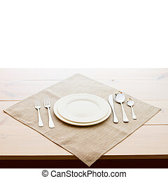 tableware for dinner - plates and forks on wooden table surface