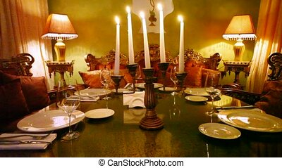 Tableware stands on table on which light candles in restaurant