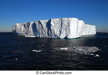 tabular iceberg floating in the blue ocean