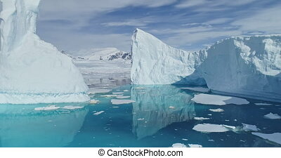 Tabular icebergs melt at turquoise ocean bay aerial. Huge high ice glacier at polar nature environment. Arctic winter landscape at global warming problem. Desert white land of snow and ice drone shot