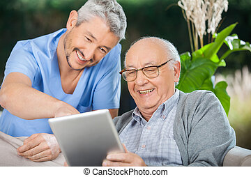 tabuleta, enquanto, computador, usando, enfermeira, desfrutando, homem sênior