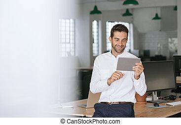 tabuleta, escrivaninha escritório, homem negócios, inclinar-se, usando, sorrindo