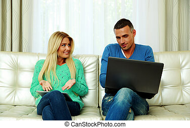 tabuleta, sentando, sofá, par, jovem, computador, usando, lar, laptop
