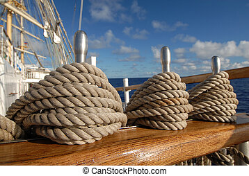 Tackle a sailing ship on a background of ocean and sky