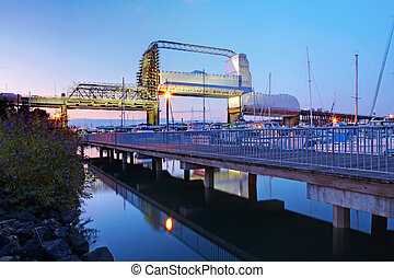 Old tacoma bridge and marina with boats in the August evening. Murray Morgan Bridge under repair.