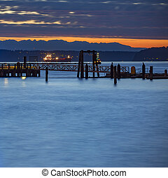 Tacoma pier over looking glowing boats at sunset