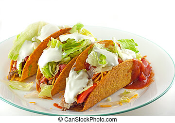 Tacos With Sour Cream Topping - Three tacos topped with sour...