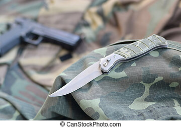 Tactical knife and pistol lie on camouflage green fabric
