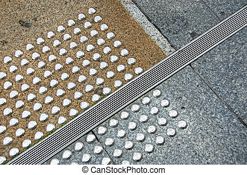 Tactile Pads - Tactile pads either side of a footpath drain
