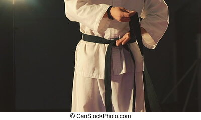 Taekwondo arts athlete tying the knot to his black belt in the gym