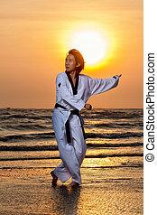 Taekwondo man training on beach