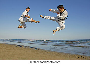 taekwondo on the beach - training of the two young men on...