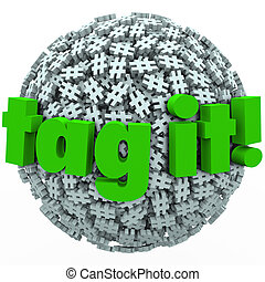 The words Tag It on a ball or sphere of hash tags to illustrate trending topics, posts or stories promoted with hashtags on news sites or social networks