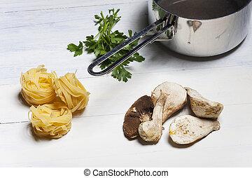 tagliatelle and edible mushrooms on wood