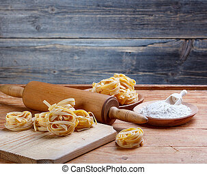 Tagliatelle on a wooden table whit rolling pin