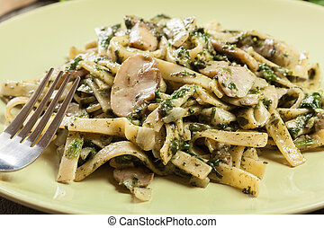 Tagliatelle pasta with spinach and mushrooms on a plate.
