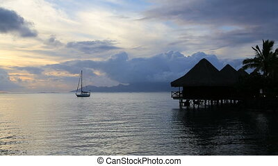 Tahiti sunset with over water bungalows and boat