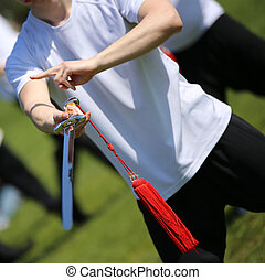 Tai Chi martial arts athlete makes motions with sword