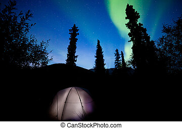 Taiga tent illuminated under northern lights flare - Tent...
