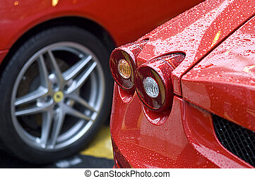 Red brake tail lights of a sports car parked alongside another