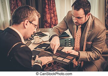 Tailor and client choosing cloth and buttons for custom made...