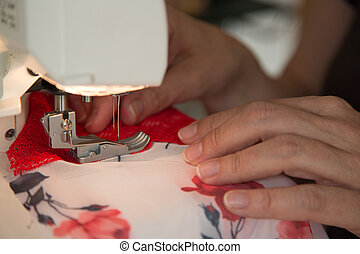 Tailor at sewing machine tailoring lingerie or a bra - Sewer...