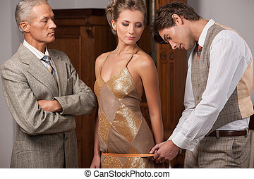 Tailor at work. Confident young tailor measuring young woman with measuring tape while man in formalwear standing near them