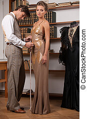 Tailor at work. Full length of confident young tailors measuring woman dress with measuring tape