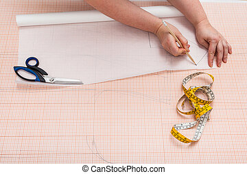 tailor copies a clothing pattern on tracing paper