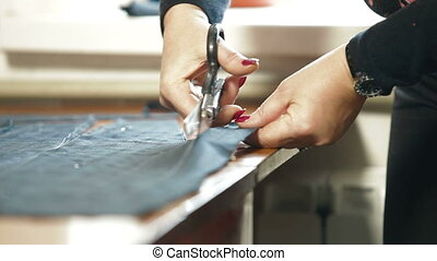 tailor cutting fabric with a taylors scissors