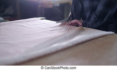 Tailor cutting fabric with scissors. Close up. Slow motion....