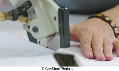Machine pulling sewing thread while tailor working with textile. Professional sewing machine in business studio with female tailor working on new shirt