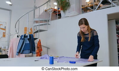 Tailor, designer drawing line on fabric at sewing studio