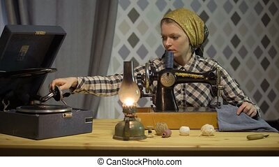 Tailor girl sews cloth with old manual hand sewing machine. Retro seamstress woman works at home or workshop at night with kerosene lamp, listens music vinyl plate, gramophone or phonograph.