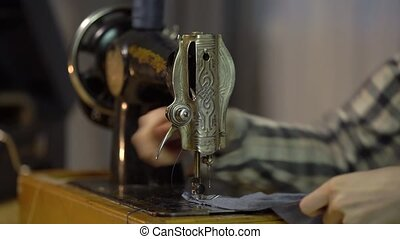 Tailor girl sews cloth with old manual hand sewing machine....