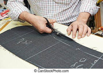Tailor hands working with scissor and suit textile cloth