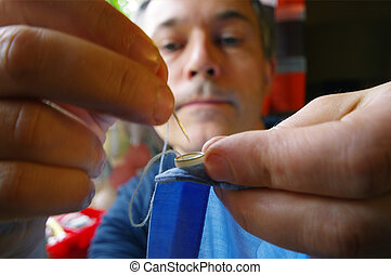 Tailor man with needle and thread in the hands