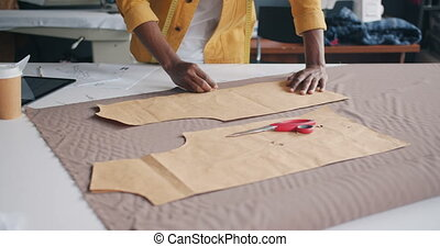 Tailor manufacturing handmade clothing outlining model on...