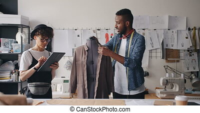 Tailor measuring clothes on mannequin while girl colleague...