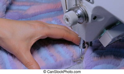 Tailor sewing fur coat with sewing machine - Close up shot -...