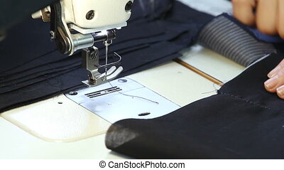 Tailor sews clothing on the sewing machine. - Closeup of...