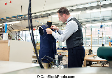 Tailor standing working on a blue jacket